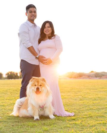 Man and pregnant woman posing towards camera, smiling with dog at their feet looking at camera.