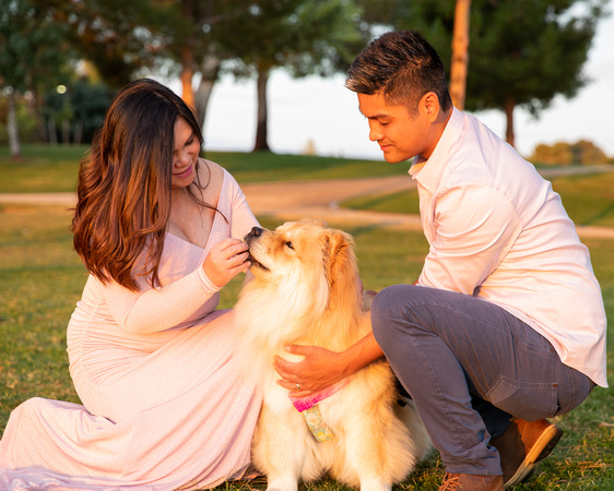 Woman and man crouching down with fluffy dog for a candid photo. Woman is giving a dog a treat, everyone is smiling.