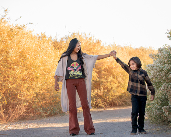 Sibling girl and little boy play on a path among tall grassy fields.